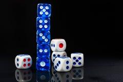 Синь и белизна dices на лоснистой черной предпосылке Стоковое Фото