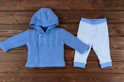 Синь младенцев связала кардиган и striped брюки на деревянном backgro Стоковые Фотографии RF