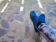 Синь обувает ногу на каменной предпосылке Стоковое фото RF