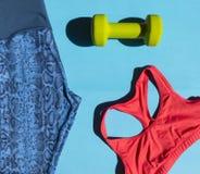 Синь резвится гетры, красные женщины спорт ` s покрывают, зеленая гантель, bl Стоковая Фотография