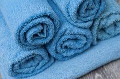 Синь свернула полотенца ванны на деревянном столе в ванной комнате Стоковое Изображение RF
