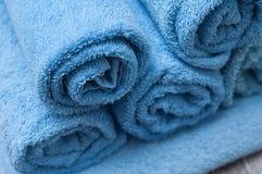 Синь свернула полотенца ванны на деревянном столе в ванной комнате Стоковые Изображения