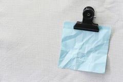 Синь сморщенной бумаги примечания помещенной на белой предпосылке ткани Стоковые Изображения