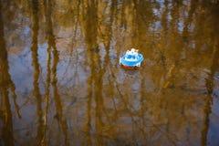 Синь шлюпки детей идет на золотую воду стоковые изображения