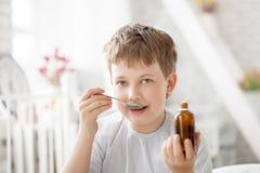Сироп кашля мальчика выпивая стоковое фото rf