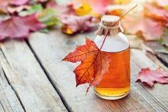 Сироп клена или здоровая тинктура и кленовые листы стоковая фотография