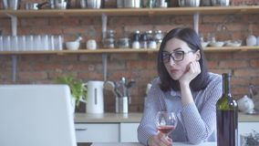 Сиротливая бизнес-леди женщины выпивает вино в кухне смотря ноутбук стоковые фото