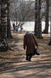 Сиротливая больная изогнутая женщина идет вдоль переулка парка стоковая фотография