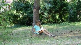 Сиротливая девушка сидя в солнечной лужайке в тени дерева читая книгу видеоматериал