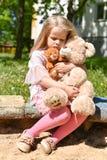 Сиротливая девушка с игрушками грустна в ящике с песком стоковые фото