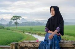 Сиротливая девушка hijab с ее улыбкой в реке и поле Стоковое Изображение RF