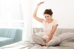 Сиротливая женщина плачет самостоятельно, ее тушь пропускала Она сидит на кровати в светлой комнате стоковое изображение