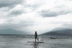 Сиротливая женщина смотрит безграничность и uncontaminated природу на бурный день стоковое изображение