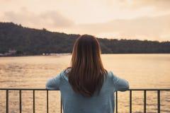 Сиротливая женщина стоя отсутствующее запомненное на реке стоковые изображения rf