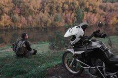 Сиротливая концепция, человек сидит самостоятельно и взгляд на расстоянии Мотоцикл приключения, мотоциклист, водитель мотоцикла с стоковое фото rf