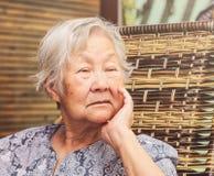 Сиротливая пожилая женщина усаженная дома, с рукой на подбородке с унылым стоковые изображения