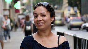 Сиротливая темн-с волосами женщина смотрит внимательно и усмехается внутри европейской улицы акции видеоматериалы