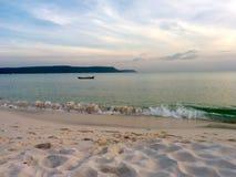 Сиротливая шлюпка на море перед заходом солнца стоковое изображение rf