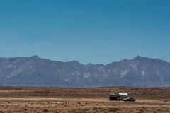 Сиротливые лачуга и автомобиль между обширным и сухим намибийским ландшафтом, против горы Brandberg стоковые изображения