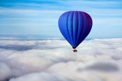Сиротливый голубой горячий воздушный шар плавает над облаками Стоковые Изображения