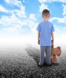Сиротливый мальчик стоя самостоятельно с плюшевым медвежонком стоковое фото