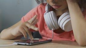 Сиротливый ребенк откладывая с smartphone, недостатком интереса, пробурил ребенка видеоматериал
