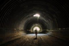 Сиротливый силуэт в темном тоннеле идет к свету Человек идя к свету стоковая фотография rf