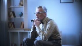Сиротливый старик полагаясь на идя ручке, мечтающ, вспоминающ молодость, ностальгия стоковые изображения