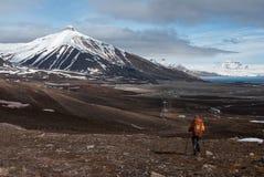 Сиротливый туристский пеший туризм к снегу покрыл гору в русском город-привидении Pyramiden в архипелаге Свальбарда стоковая фотография