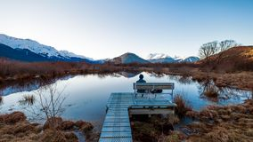 Сиротливый человек сидя на стенде в Glenorchy, Новой Зеландии стоковые изображения
