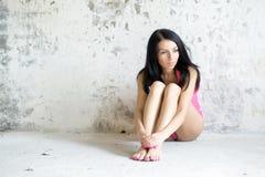Сиротливая девушка в нижнем белье сидит на стене Стоковые Фотографии RF