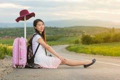 Сиротливая девушка сидя на дороге Стоковая Фотография