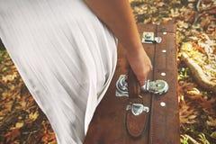 Сиротливая женщина с чемоданом идя в лес день осени стоковые фотографии rf