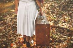 Сиротливая женщина с чемоданом идя в лес день осени стоковые фото