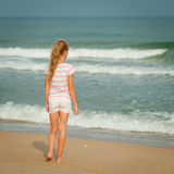 Сиротливая маленькая девочка идя на пляж стоковая фотография