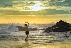Сиротливая молодая женщина стоит самостоятельно на пляже смотря к концу обширного горизонта Стоковые Фотографии RF