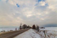 Сиротливая дорога зимы которая идет к термине Вокруг снега очень красивые облака на заходе солнца Стоковые Изображения RF