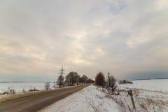 Сиротливая дорога зимы которая идет к термине Вокруг снега очень красивые облака на заходе солнца Стоковая Фотография RF