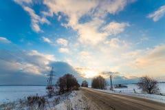 Сиротливая дорога зимы которая идет к термине Вокруг снега очень красивые облака на заходе солнца Стоковые Фото