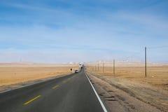 Сиротливая дорога пустыни в ясном дне неба Стоковые Изображения
