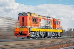 Сиротливая спешка локомотива поездом спешит рельсом в городе Стоковое Изображение RF