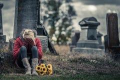Сиротливая унылая молодая женщина в оплакивать перед могильным камнем стоковое фото