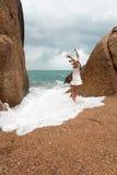 Сиротливая худенькая женщина на дезертированном пляже на предпосылке больших камней и темного облачного неба Она подняла ее оружи Стоковое Изображение