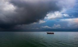 Сиротливая шлюпка во время бурного восхода солнца, красочные облака Стоковые Изображения RF