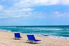 Сиротливые голубые стулья на песочном океане приставают к берегу Стоковые Изображения RF