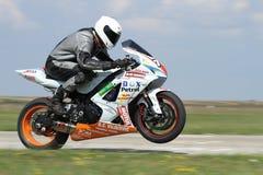 Сиротливый гонщик мотоцилк на следе поднял на заднем колесе Стоковое Изображение