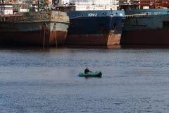Сиротливый рыболов на шлюпке около большого корабля Стоковая Фотография