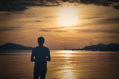 Сиротливый силуэт человека стоя перед морем стоковая фотография rf