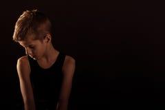 Сиротливый тонкий мальчик против черноты с космосом экземпляра стоковые фотографии rf