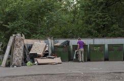 Сиротливый человек роясь в мусорном контейнере Стоковое Фото